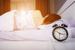 时钟展示上午10点 并且睡觉在与阳光的床上的妇女在平均观测距离 免版税图库摄影