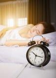 时钟展示上午10点 并且睡觉在与阳光的床上的妇女在平均观测距离 库存照片