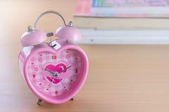 时钟桃红色甜心形状在木背景的 库存照片
