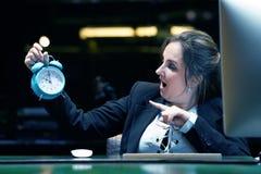 时钟藏品妇女 妇女在工作场所在她的手上拿着一个闹钟 免版税库存照片