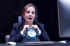 时钟藏品妇女 妇女在工作场所在她的手上拿着一个闹钟 库存照片
