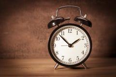 时钟-在袋布和木背景的葡萄酒老闹钟 免版税库存图片