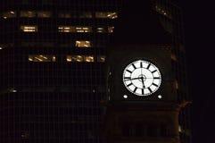 时间在黑暗偷偷地走,即使您穿上t通知 在摩天大楼前的多伦多老市政厅钟楼夜 免版税库存照片