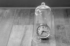 时间安排概念:关闭红色葡萄酒闹钟被变形和在木地板上的损坏的设置在玻璃圆顶 免版税图库摄影