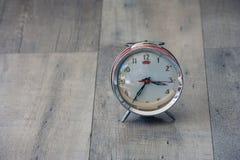 时间安排概念:关闭红色葡萄酒闹钟被变形和在木地板上的损坏的设置 库存图片