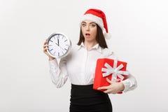 时间安排概念-有拿着时钟和礼物的圣诞老人帽子的年轻女商人被隔绝在白色背景 库存照片