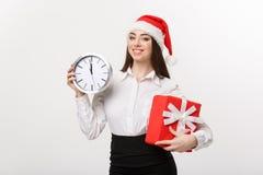 时间安排概念-有拿着时钟和礼物的圣诞老人帽子的年轻女商人被隔绝在白色背景 免版税库存图片