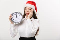 时间安排概念-有拿着时钟的圣诞老人帽子的年轻女商人被隔绝在白色背景 库存照片