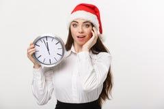 时间安排概念-有拿着时钟的圣诞老人帽子的年轻女商人被隔绝在白色背景 库存图片