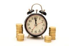 时间是与硬币堆的金钱概念在时钟附近 免版税库存照片