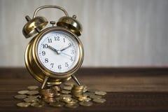 时间是珍贵的概念 在硬币的金黄闹钟 免版税库存照片