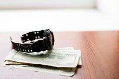 时间是货币 一百美元和黑手表在木桌上 免版税库存图片