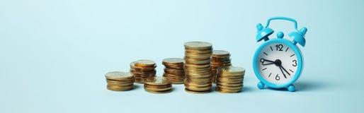 时间是金钱概念 闹钟和金黄硬币 现金投资的财政选择 免版税图库摄影