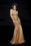 时髦。在金黄黄色礼服的美好的时装模特儿在黑色 库存照片