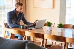 时髦人士读书报纸在他的现代餐桌上 库存图片