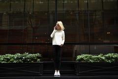 年轻时髦和亭亭玉立的女孩站立在餐馆附近和谈话在电话 图库摄影