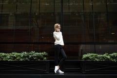 年轻时髦和亭亭玉立的女孩站立在餐馆附近和谈话在电话 免版税图库摄影