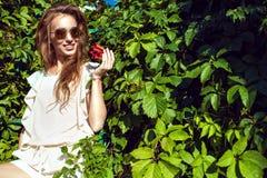 时髦回合的美丽的微笑的妇女反映了太阳镜坐梯子在与开花的弗吉尼亚爬行物树篱 图库摄影