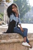 时髦地礼服美国黑人的女孩的全长vieww谈话通过手机和笑 她坐 库存照片