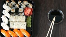 时髦地被放置的寿司在黑木背景设置了在酱油和中国竹棍子旁边 滚多种寿司 股票录像