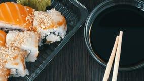 时髦地被放置的寿司在黑木背景设置了在酱油和中国竹棍子旁边 滚多种寿司 影视素材
