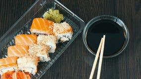 时髦地被放置的寿司在黑木背景设置了在酱油和中国竹棍子旁边 滚多种寿司 股票视频