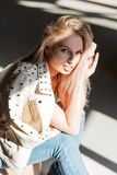 时髦夹克的俏丽的可爱的年轻女人时装模特儿金发碧眼的女人在葡萄酒牛仔裤在一个灰色演播室坐并且享用 库存图片