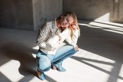 时髦夹克的时髦的现代年轻白肤金发的妇女在摆在坐的绿色时兴的牛仔靴的蓝色被剥去的牛仔裤户内 免版税图库摄影