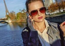 年轻时髦妇女谈话在手机在埃佛尔铁塔附近 免版税图库摄影