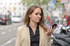 时髦妇女读sms在她的机动性 免版税库存图片