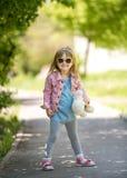 时髦小女孩在有teddybear手中的公园 免版税库存图片