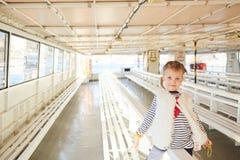 时髦小女孩获得一个乐趣在空的游览船 免版税库存照片