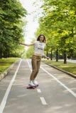时髦少妇在一条道路乘坐longboard在公园户外在夏天 溜冰板运动 户外, 免版税库存图片