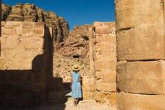 时髦帽子的典雅的女性游人和蔚蓝色礼服探索失去的岩石城市Petra 浪漫心情 大气地方 启远地夏天 免版税库存图片