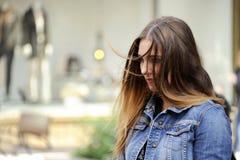 时髦年轻行家妇女哀伤地看下来与一根邋遢的头发 免版税图库摄影