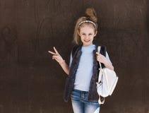时髦成套装备的迷人的八岁的女孩有在街道上的一个背包身分的在一好日子 免版税图库摄影