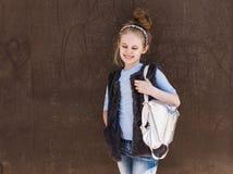 时髦成套装备的迷人的八岁的女孩有在街道上的一个背包身分的在一好日子 库存照片