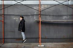 时髦成套装备的年轻时髦的红头发人人有乐趣和跳对都市墙壁户外 图库摄影