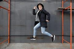 时髦成套装备的年轻时髦的红头发人人有乐趣和跳对都市墙壁户外 免版税库存图片