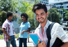 时髦拉丁男学生室外在有朋友的校园里 免版税库存照片