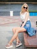 时髦摆在河附近的太阳镜牛仔裤微型裙子的年轻可爱的白肤金发的学生女孩在公园,享受温暖的太阳光, recre 免版税库存照片
