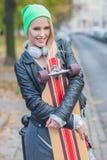 时髦服装拥抱滑板的俏丽的妇女 图库摄影