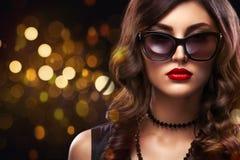 时髦样式美丽的妇女特写镜头画象  在黑背景的长的卷曲深色的头发与光 St华伦泰 免版税库存照片
