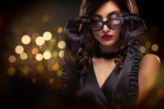 时髦样式美丽的妇女特写镜头画象  在黑背景的长的卷曲深色的头发与光 St华伦泰 免版税库存图片