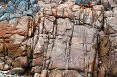 时髦橙红岩石纹理墙壁 免版税库存照片