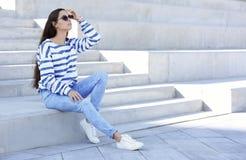 时髦牛仔裤坐的年轻行家妇女 图库摄影