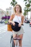 时髦现代女性摆在照相机的,当站立与她在街道的减速火箭的自行车在多云天时 库存照片