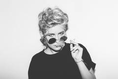 时髦的一件黑T恤杉和岩石太阳镜的时尚性感的白肤金发的坏女孩抽烟 危险岩石情感妇女 库存照片