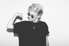 时髦的一件黑T恤杉和岩石太阳镜的时尚性感的白肤金发的坏女孩 危险岩石情感妇女 空白 免版税库存照片