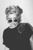 时髦的一件黑T恤杉和用香烟盖的岩石太阳镜的时尚性感的白肤金发的坏女孩抽烟 危险 免版税库存照片